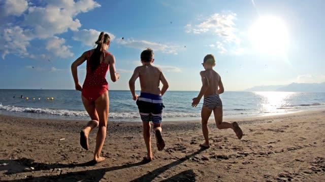 troje dzieci bawi się biegając do morza - beach filmów i materiałów b-roll