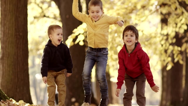 Three kids having fun with autumn leaves video