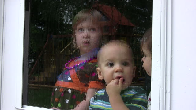 Three Kids looking through glass with rain 2 HD video