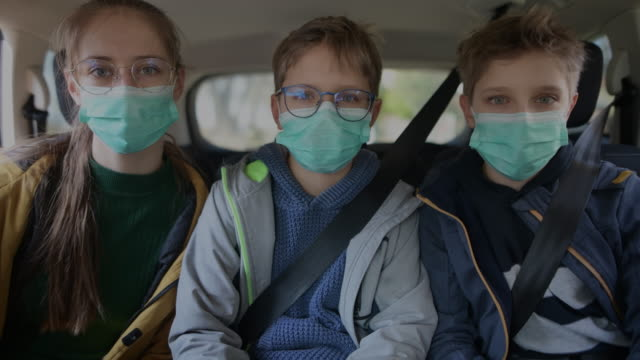 three kids wearing anti virus marks travelling by car - mask стоковые видео и кадры b-roll