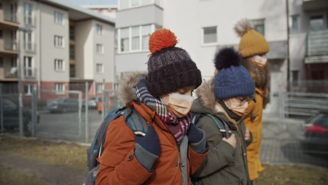 three kids wearing anti virus masks going to school - mask filmów i materiałów b-roll