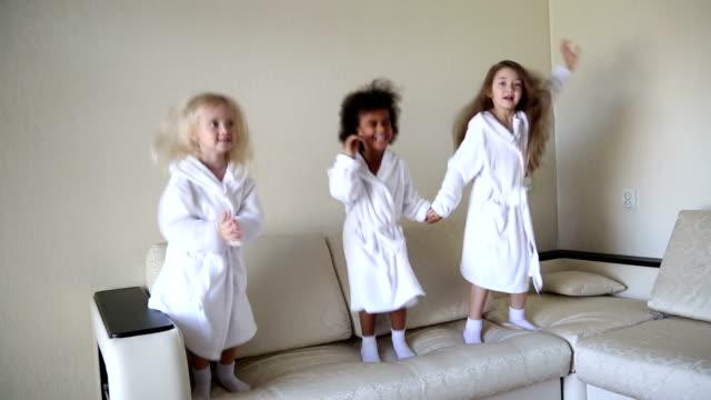 vidéos et rushes de trois petites filles sont ruent sur le canapé. - peignoir