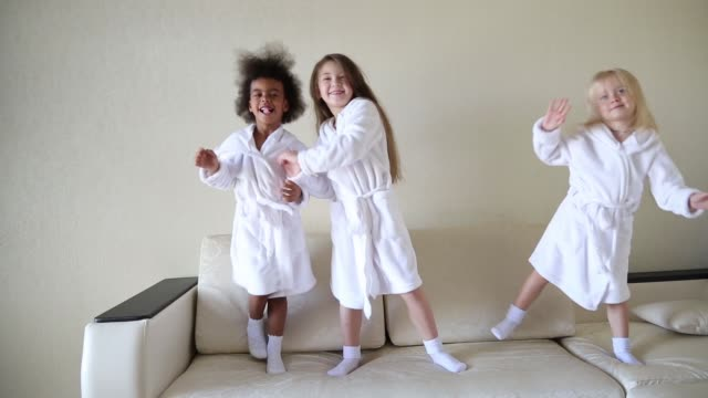 Three little girls are jumping on the couch.