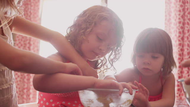 Three little girls eating cookie dough out of a mixing bowl video
