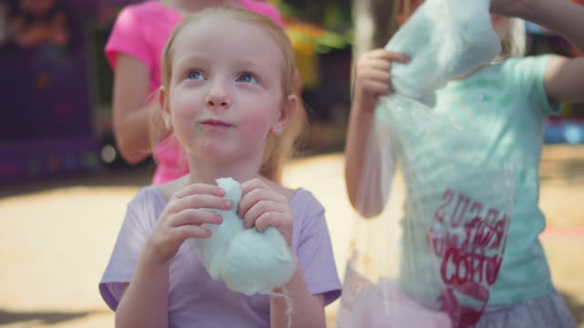 Three little girls eating cotton candy and making funny faces, in slow motion video