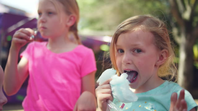 Three little girls eating cotton candy and making funny faces, in slow motion Three little girls eating cotton candy and making funny faces, in slow motion cotton candy stock videos & royalty-free footage