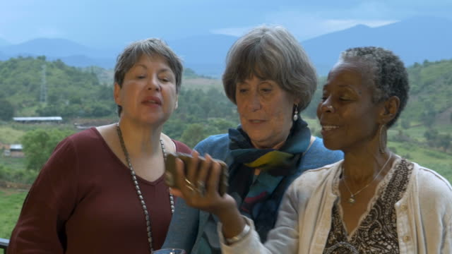 Three lively senior women in 60s on vacation taking selfies with smart phone video