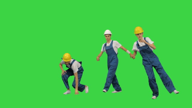 Three male construction workers in hard hats hoping into the camera spot, break dancing and jumping away on a Green Screen, Chroma Key Full length shot. Front view. Three male construction workers in hard hats hoping into the camera spot, break dancing and jumping away on a Green Screen, Chroma Key. Professional shot in 4K resolution. 045. You can use it e.g. in your medical, commercial video, business, presentation, broadcast craftsman architecture stock videos & royalty-free footage