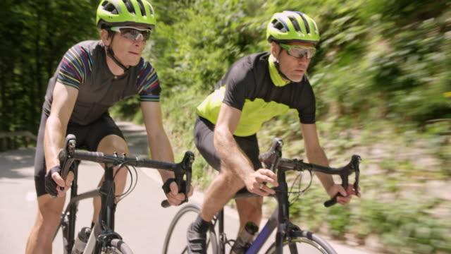 three male cyclists riding road bikes down the mountain road in sunshine - ciclismo su strada video stock e b–roll