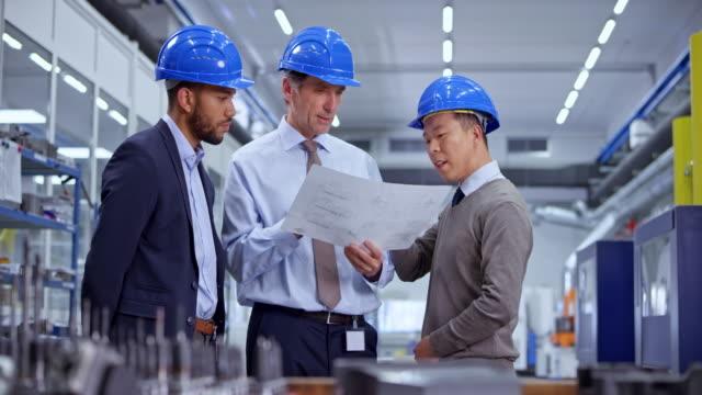 ds工場に立つ計画を見ながら話す3人の男性エンジニア - 機械部品点の映像素材/bロール