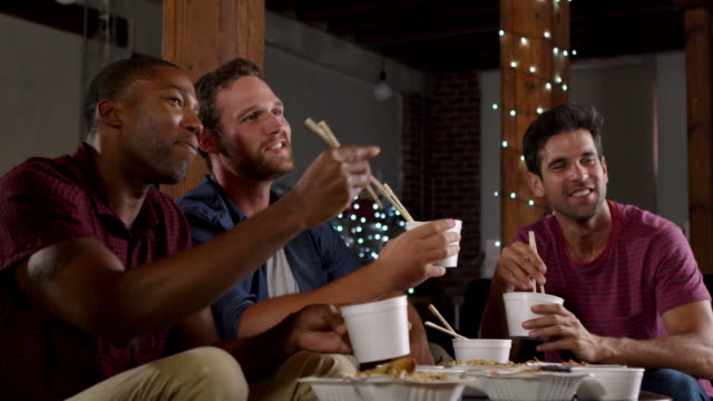 Three male friends eating a Chinese take-away watching TV, shot on R3D video