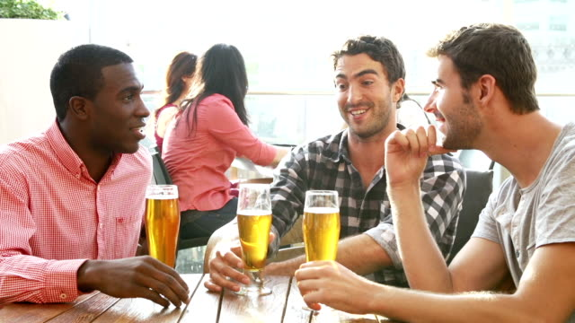 Three Male Friends Enjoying Drink At Outdoor Rooftop Bar video