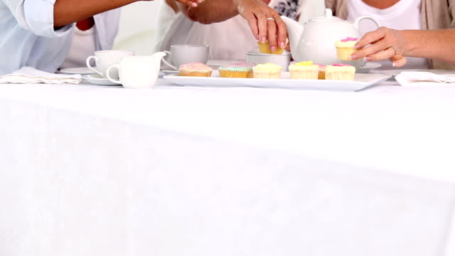 Three mature friends having cup cakes video