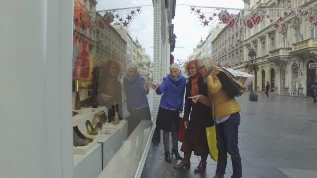 tre mogna kvinnor ute i shopping - spendera pengar bildbanksvideor och videomaterial från bakom kulisserna