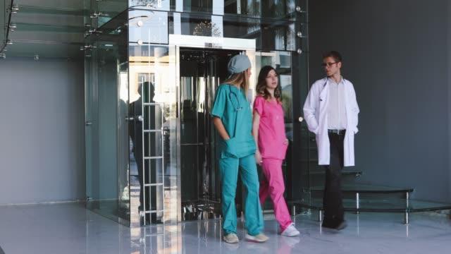 drei mediziner, die entlang des krankenhauskorridors laufen - menschliche tätigkeit stock-videos und b-roll-filmmaterial