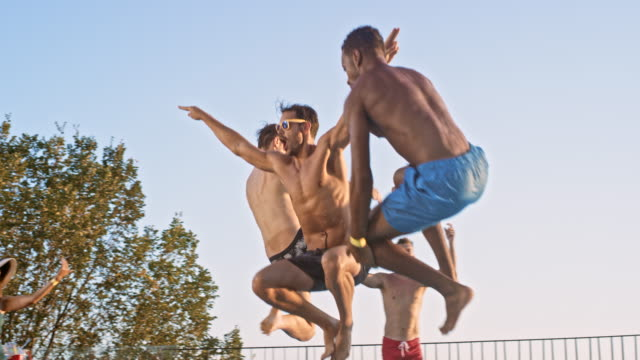 SLO MO DS Three men jumping into the pool together at sunset and their friends are clapping their hands and laughing Slow motion wide low angle handheld shot of three men jumping into the water at a pool party at sunset while being encouraged by their friends. Shot in Slovenia.Slow motion wide low angle handheld shot of three men jumping into the water at a pool party at sunset while being encouraged by their friends. Shot in Slovenia. pool party stock videos & royalty-free footage