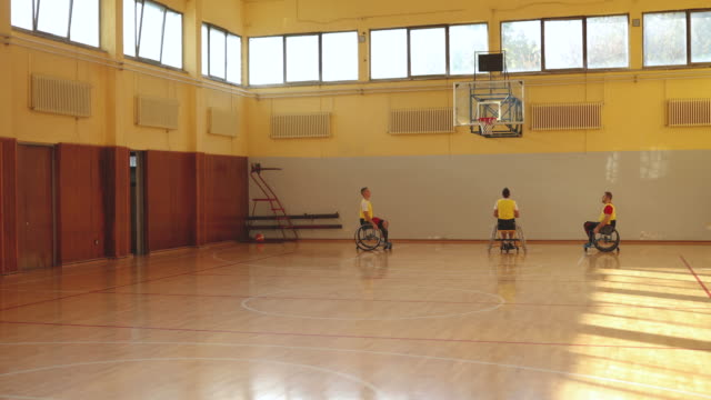 Three men playing basketball in the wheelchair