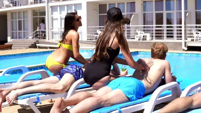 Three men receiving massage from attractive young girls in bikini lying on coaches by the pool at a beautiful villa and drinking beer. Slowmotion shot. video