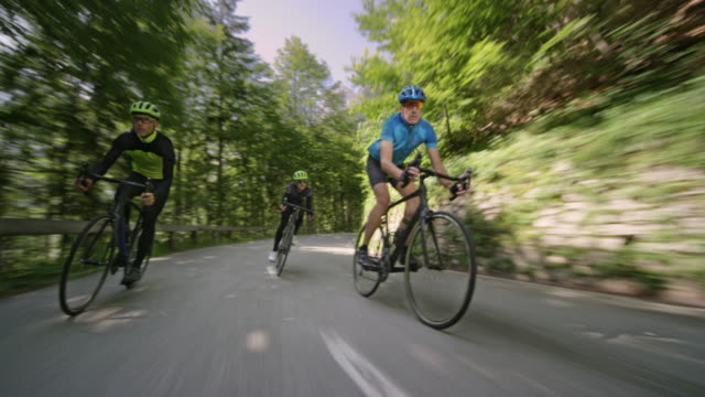 Three men riding road bikes down an asphalt mountain road on a sunny day
