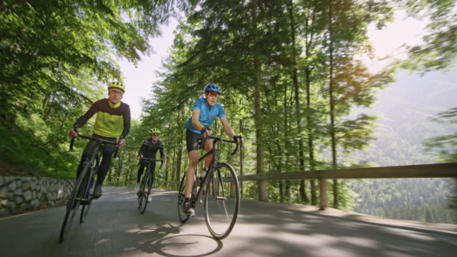 three men riding road bikes up an asphalt mountain road on a sunny day - passo montano video stock e b–roll