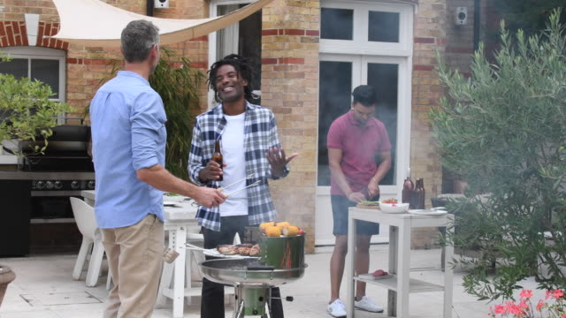Tres hombres de pie en el jardín con barbacoa y riendo - vídeo