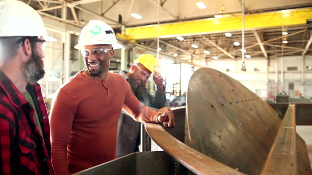 Three men working in metal fabrication shop, talking Two multi-ethnic workers in a metal fabrication shop, standing beside a large metal object, talking. They are joined by a third man. manufacturing occupation stock videos & royalty-free footage