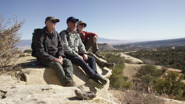 Three Middle-Aged Men Sit on a Rock in the Desert Mountains of Western Colorado to Talk and Admire the View on a Clear, Sunny Day
