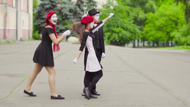 Three mimes act in the city street Company of three mimes, man and women in black dress do perfomance in the city. One girl is taking different heroic poses and her colleagues shake her hair and help her. Performance of street artists. greasepaint stock videos & royalty-free footage