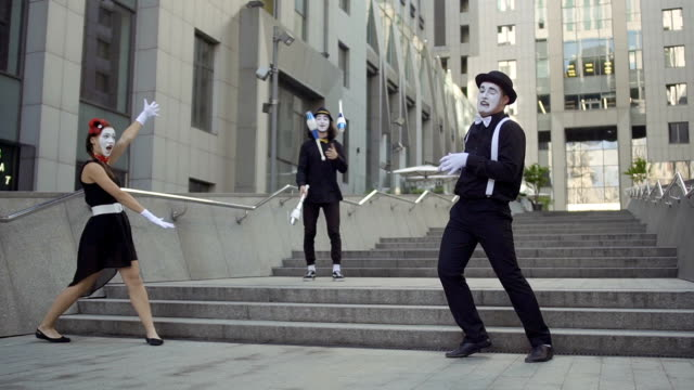 Three mimes at office center background Three funny mimes play a scene. Girl and guy gesticulates their facial expressions. Other guy juggling with pins. Young amateurs earn money showing people small funny scenes at urban streets. greasepaint stock videos & royalty-free footage