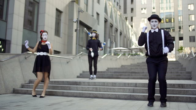 Three mimes have fun standing near office center Three funny mimes play a scene. Girl and guy gesticulates their facial expressions. Other guy juggling with pins. Young amateurs earn money showing people small funny scenes at urban streets. greasepaint stock videos & royalty-free footage