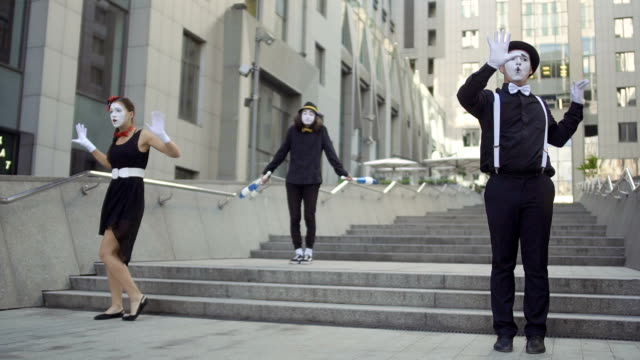 three mimes play a scene for people at office center background - гримировальные краски стоковые видео и кадры b-roll