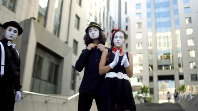 Three mimes want to be better than their colleagues Three mimes want to be better than their colleagues. Girl and guys gesticulates hands and facial expressions. Young amateurs earn money showing small funny scenes at the street. greasepaint stock videos & royalty-free footage