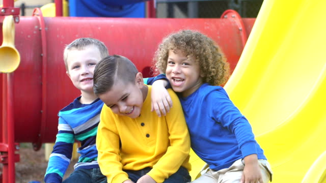 Three mischievous boys on playground A group of three multi-ethnic preschool boys, 5 and 6 years old hanging out together on the playground, sitting on a slide. One is making silly faces at the camera. child care stock videos & royalty-free footage