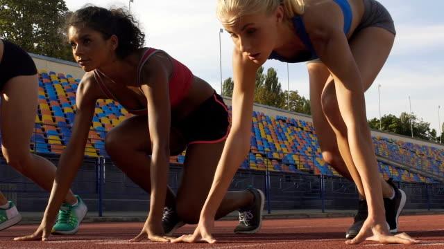 yarış, slowmotion önce bir başlangıç çizgisi üzerinde üç karışık ırk kadının... - pist stok videoları ve detay görüntü çekimi