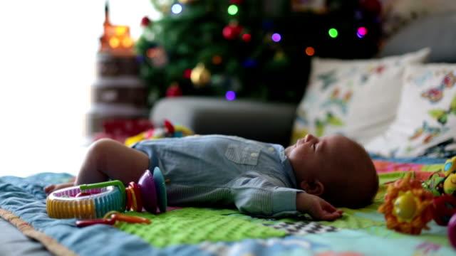vídeos de stock, filmes e b-roll de menino de três meses de idade, chorando em casa em um cobertor de atividade coloridos, brinquedos e diferentes atividades em torno dele - mobile