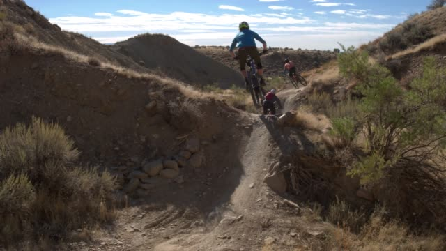 three mountain bikers with a dog jump on 18 road in fruita, colorado - bike tire tracks video stock e b–roll