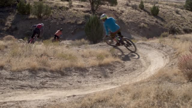 three mountain bikers with a dog ride around a curved trail on 18 road in fruita, colorado - bike tire tracks video stock e b–roll