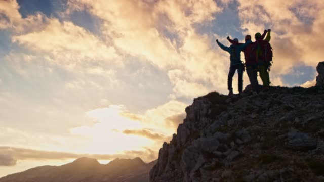 three mountaineers doing a high five on mountain top at sunset - trekking video stock e b–roll