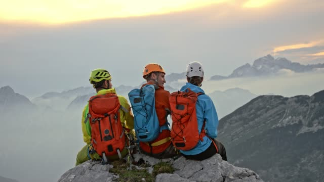 three mountaineers sitting on the edge on the mountain top and talking - альпинизм стоковые видео и кадры b-roll