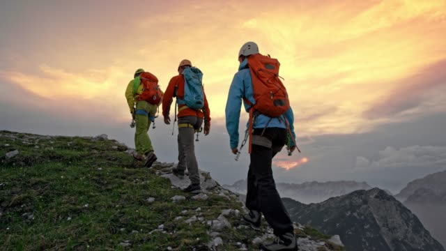 Three mountaineers walking on a mountain ridge at sunset