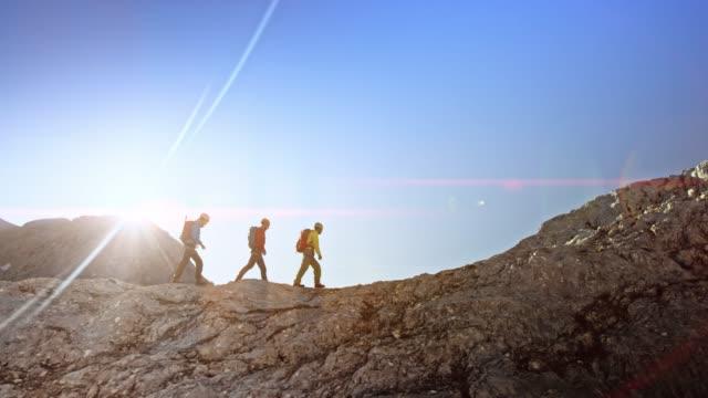 Three mountaineers walking on a rocky mountain ridge in sunshine