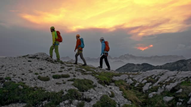 three mountaineers walking on the mountain top at sunset - tre persone video stock e b–roll