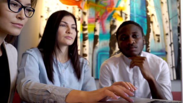 Three Multi ethnic designers check their project on the laptop in their stylish modern office video
