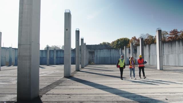 tre ingegneri multietnici che camminano su un cantiere vuoto - attrezzatura edilizia video stock e b–roll