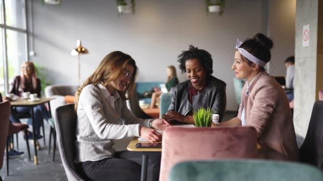 three multi-ethnic female friends drinking coffee in cafeteria - коллега стоковые видео и кадры b-roll