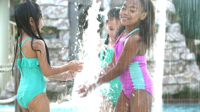 Three multi-ethnic girls playing in water fountains