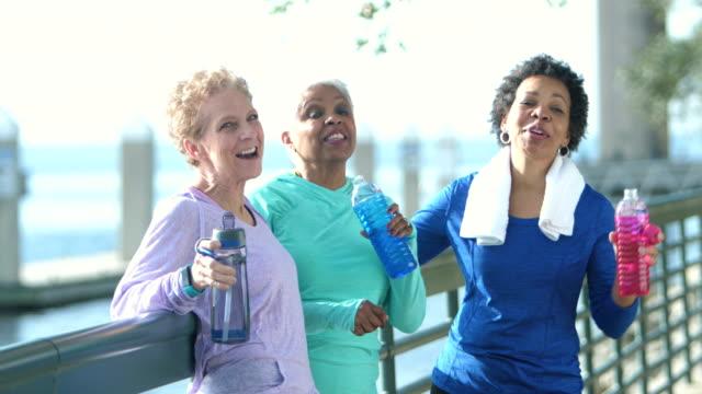 vídeos de stock e filmes b-roll de three multi-ethnic mature and senior women talking and laughing - 55 59 anos