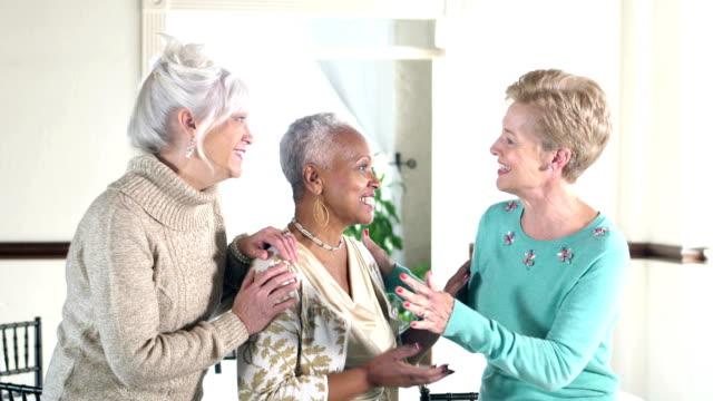 Three multi-ethnic senior women conversing video