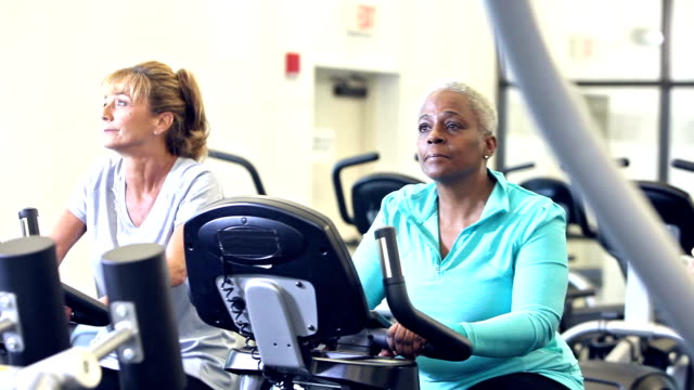 Three multi-ethnic women riding exercise bikes in gym video