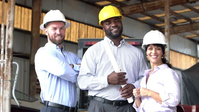 Three multi-ethnic workers wearing hardhats - video